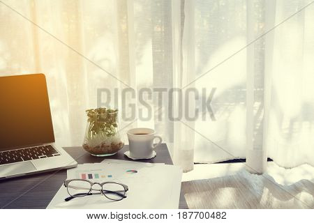 office table with blank screen on laptop coffee cup garden plant pot and statistic report paper ob blurry drape at living room concept of business lifestyle. focus from front office table.