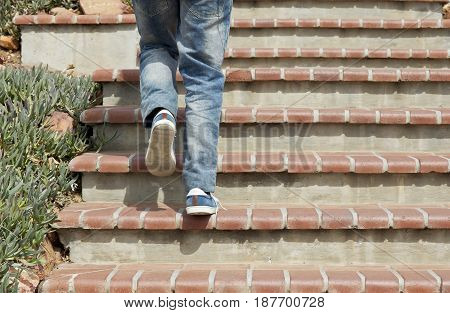 young male walking up cement stairs wearing jeans and shoes