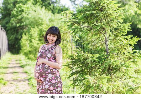 Pregnant woman posing in the summer park.