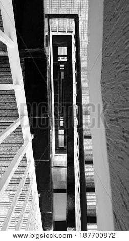 Abstract view of a stairwell with black banisters and tiled floors
