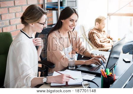 Cheerful busy manager is typing on laptop. Her colleague watching it with interest and holding pencil