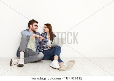 Happy loving couple with laptop. Man showing project to woman on computer, pointing on screen, white background, studio shot