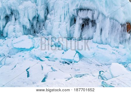 Frozen water and Icicles covered with snow at rock island in Lake Baikal in winter