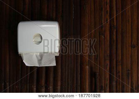 toilet paper in paper tower dispenser on woven wood