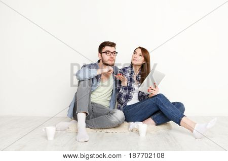 Couple selecting online furniture for new apartment while sitting on floor in empty living room, white background