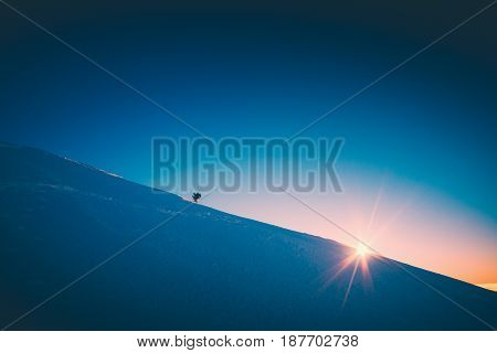 A climber climbs up a snowy slope. Sunset sky on a horison. Instagram stylisation.