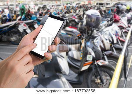 human hand hold smartphone tablet cell phone on blurry parking motorcycle. concept of trace vehicle online.