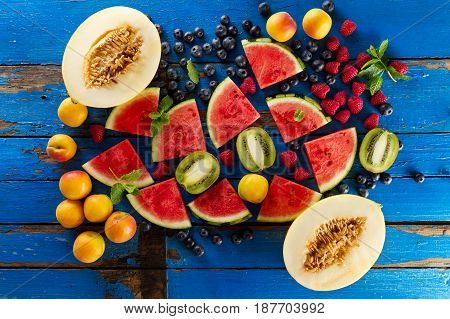 Variety of tasty fresh healthy appetizing fruits on blue wooden rustic table. Food Summer Concept.
