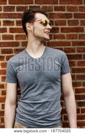 Pretty handsome young man hipster with sunglasses smiling laughing behind red brick wall. Looking aside.