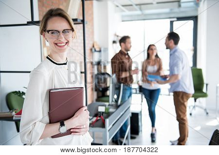 Cheerful manager is standing near shelf and looking at camera with bright smile. Her colleagues discussing certain issue. Portrait