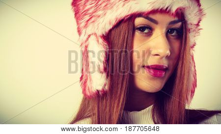 Winter clothing fashion concept. Closeup of young mulatto woman wearing red white fur cap. Mixed race girl in wintertime clothes studio shot