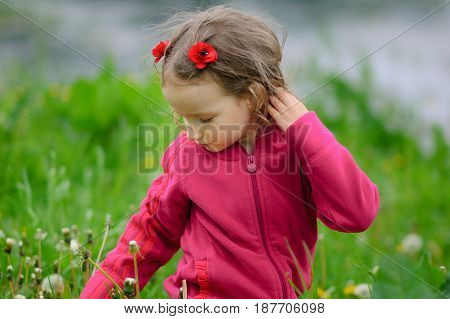 The cut girl carefully examines the blade of grass, sitting on a spring clearing. The child knows the world. Children Protection Day.