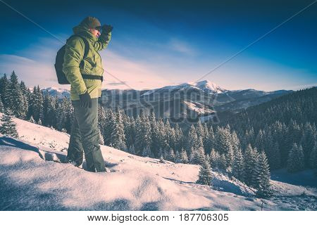 Hiker standing on a hill covered with snow against winter mountain landscape and looking to the horizon. Backpacker on a top. Instagram stylisation.