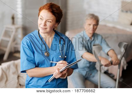 Connecting facts. Distinguished successful local therapist visiting her patient at home and writing down his symptoms in her journal while running a consultation