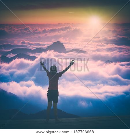 Little childe standing on a wooden flooring with raised hands above the mountain valley in a light of sunrise. Instagram stylisation.