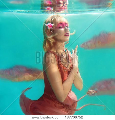 portrait of beautiful blonde woman with pink flamingo flying underwater in the swimming pool
