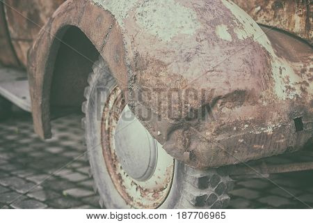 Rusty crumpled front wing with the wheel and tire vintage car