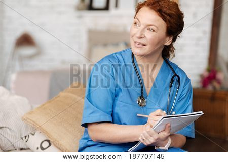 Questioning for understanding. Successful great local therapist visiting the patient at home and running a consultation while writing down important data in her journal