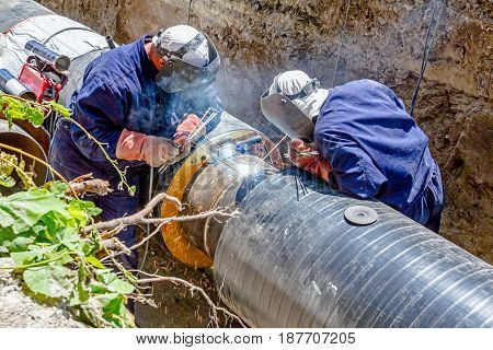 Team of welders is in trench working hard to install a new pipeline. Arc welding pipes