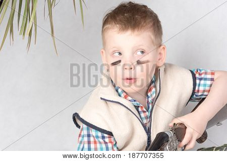 Little boy with black lines on face is hunter playing
