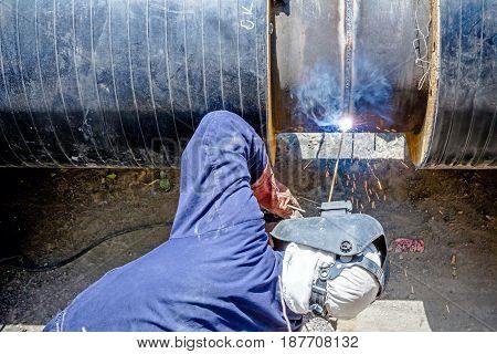 Welder is in trench working hard arc welding pipeline.