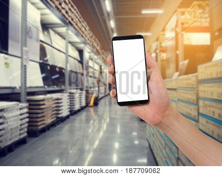 hand hold smartphone tablet cell phone on blurry storehouse concept of Ordering product online.
