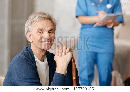 Convenience for the elderly. Competent caring local therapist delivering professional assistance at home while the patient seeming delighted and sitting on the sofa