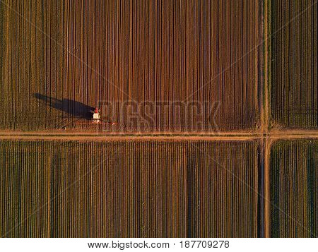 Agricultural tractor with crop sprayer in cultivated corn maize crop field drone pov top view