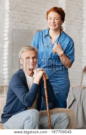Preventing the illness. Delighted charismatic motivated woman conducting a consultation for an elderly patient while paying him a visit and using professional equipment for checkup