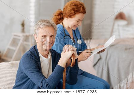 A moment to analyze. Handsome charismatic elderly man undergoing a regular examination and waiting for results of his tests while the doctor analyzing obtained data