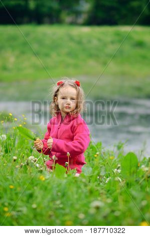 A small girl is sitting alone in the grass on the bank of a lake, a river. The child looks seriously at the lens. Concentrated look, curly hair, fleece jacket.. Children Protection Day.