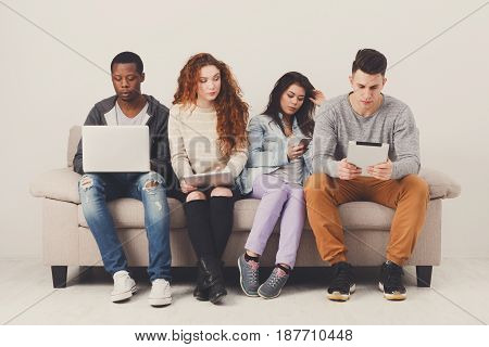 People with gadgets, addiction concept, copy space. Friends sitting on sofa indoors and working on project