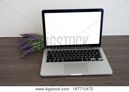 Office table with blank screen on laptop and beautiful lavender flower . View from side office table Business time concept.