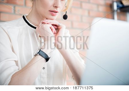 Manager in equipment for work is putting arms under chin. She sitting afore laptop. Low angle