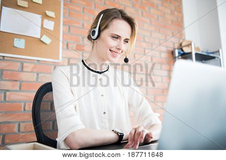 Cheerful female employee in headphones is looking at laptop with smile. She using gadget for work. Low angle