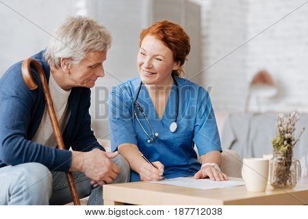 Some formalities. Excellent experienced medical worker telling her patient about services she providing while he wanting hiring her for taking care of him
