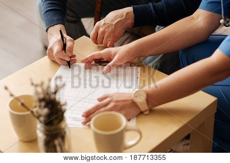 Confirming recruitment. Intelligent pleasant ill gentleman signing the contract with qualified medical worker who providing him with private competent services at home