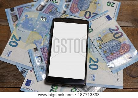 Amounts of euro banknotes and a mobile phone on an old wood
