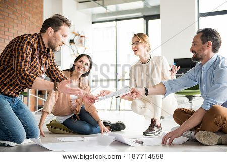 Happy interested managers are situated on floor. Cheerful man is giving sheet of paper to astonished colleague. Women looking at them with smile