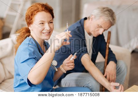 Precise procedure. Qualified trained medical worker using a sterile syringe for injecting some vitamins needed for boosting patients immune system