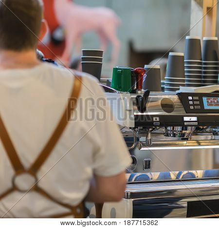 Professional barista, working at the bar. Making coffee in the coffee machine. Fresh espresso.. Coffee culture and professional coffee making, service and catering concepts
