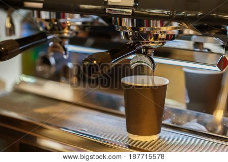 Close-up fresh espresso pours in paper cup, Italian espresso machine. Coffee culture and professional coffee making, service and catering concepts