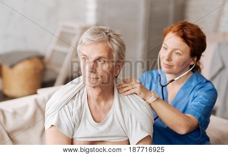 Breathe calmly. Handsome thoughtful aged gentleman receiving a visit from his doctor who using stethoscope for testing his lungs