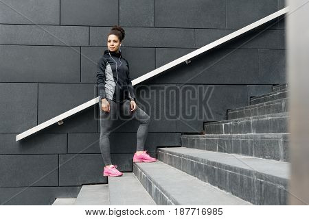 Female jogger resting after running, standing on staircase