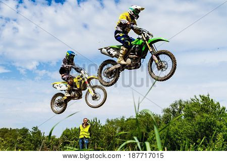 Uzhgorod Ukraine - May 21 2017: Unidentified riders in action against the sky on the Championship of Zakarpatie region on motocross on May 21 2017 in Uzhgorod Ukraine.