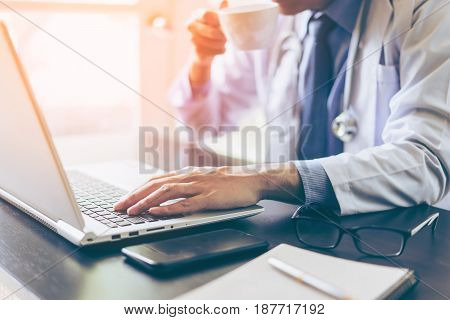 Hands of doctor using his laptop computer with drinking coffee on working table