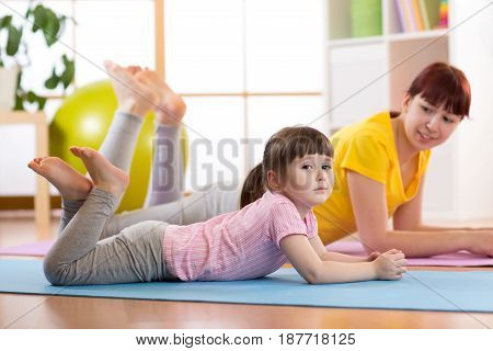 Mother and kid daughter doing gymnastics exercises on mat at home.