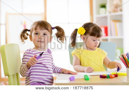 Kids drawing in kindergaten. Children paint in nursery. Preschooler with pen at home. Creative toddlers.