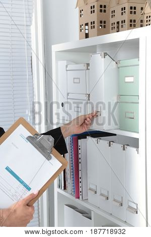 Business woman takes a folder that is on the shelf in the office