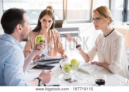 Curious female employees are looking at male colleague with light smile. He holding green apple